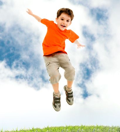 leaping: Photo of young boy jumping and raising hands in outside
