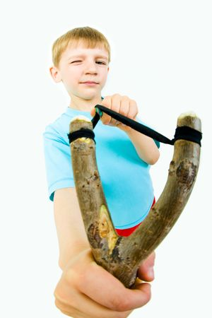 Photo of young boy holding slingshot in front of himself and looking at camera with one eye closed photo