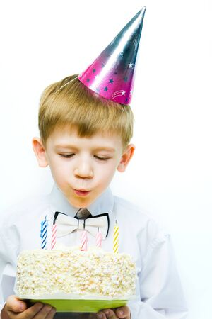 Image of boy blowing on the candles placed in the cake   photo