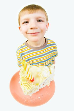 Photo of small happy boy holding saucer with birthday cake in his hand photo