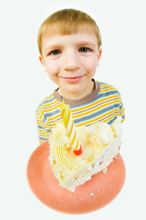 fare: Photo of saucer with a piece of birthday cake on it on the background of cute boy's face looking at camera