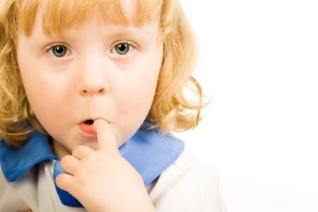 expressing: Portrait of cute little girl putting her finger to the mouth and looking at camera