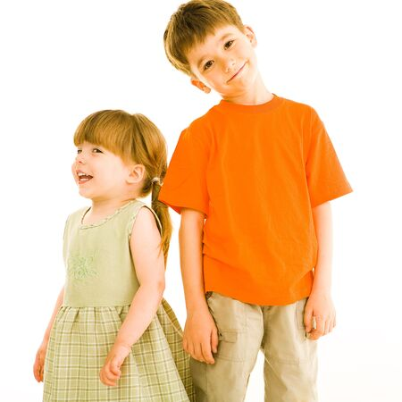 next to each other: Portrait of small sister and brother standing next to each other over white background