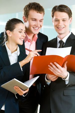 Vertical image of three business partners standing and discussing documents photo