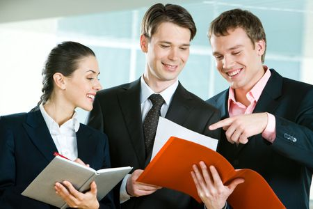 Image of business team in suits discussing papers in man's hand  photo
