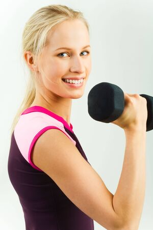Portrait of young sporty girl holding barbell in her hand isolated over white background photo