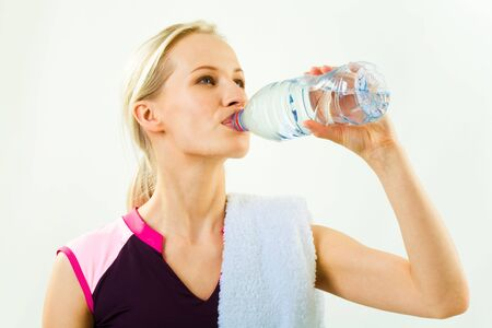 Portrait of young pretty girl drinking water from bottle with towel on her shoulder photo