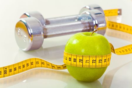 dietician: Photo of green apple tied with measuring tape on the background of metallic dumbbells