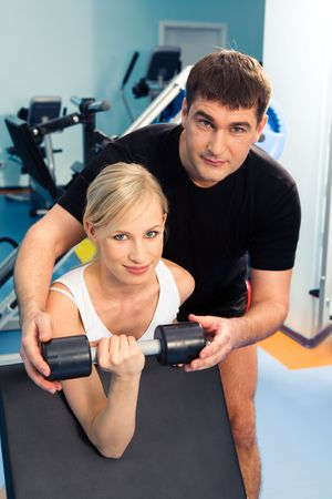 Blonde woman lifting weight with man assisting her in the sport club  photo