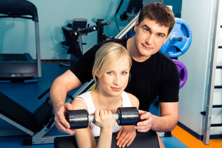 Image of trainer assisting young woman in the health club Stock Photo - 3115703