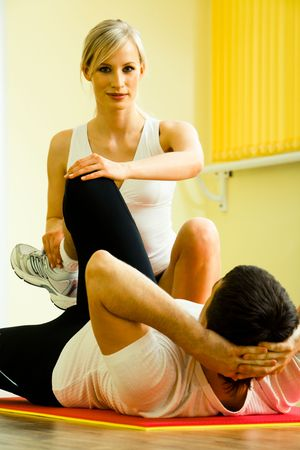 Image of young fitness instructor touching man's leg while he doing physical exercises photo