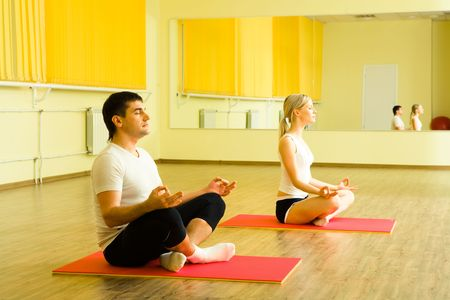 Photo of young man and woman sitting together on the floor of gym and meditating photo