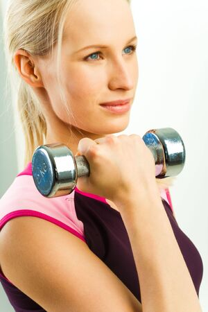 Young sports woman holds black barbell in her hand  photo