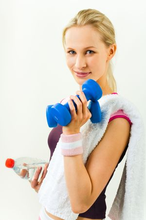 Sports lady holding white towel, blue dumbbell and bottle of water  photo