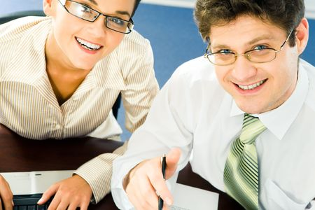 Close-up of smiling business partners at work looking upwards at camera  photo