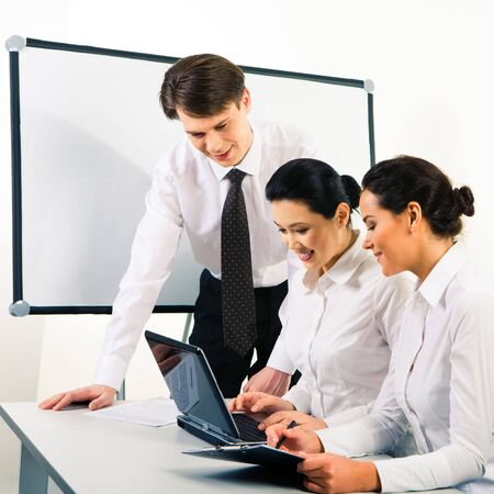 Image of modern business team working at new project during meeting and looking at laptop monitor photo