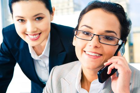 Close-up of businesswoman speaking on the phone and looking at camera with her colleague at the background photo