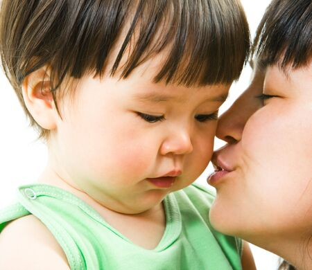 Close-up of mother kissing her small daughter lovingly over white background photo