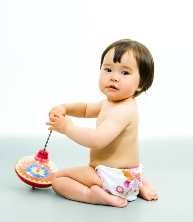 Photo of cute baby sitting in the floor and playing with whirling top