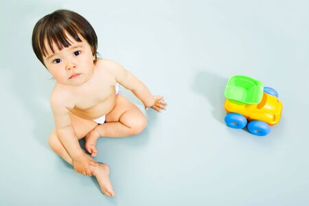 Image of adorable little girl sitting with toy near by  Stock Photo - 3133705