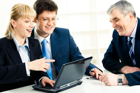 Photo of successful people in front of laptop while woman pointing at its monitor with astonishment photo