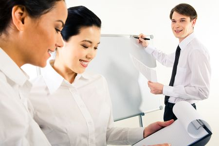 Close-up of business ladies planning their work with happy man near whiteboard at background Stock Photo - 3146144