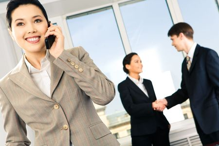 Portrait of happy woman calling on the phone on the background of business people's handshake