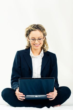 Businesswoman in suit sitting with laptop and looking at its screen over white background photo