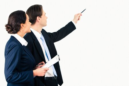 Portrait of businessman pointing at wall with woman near by  photo