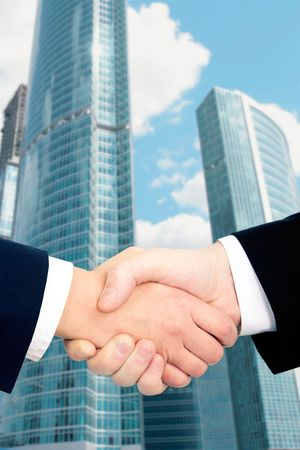 Conceptual photo of businessmen�s handshake on the background of modern buildings photo
