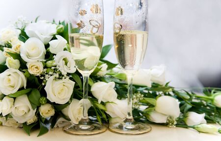 Photo of two glasses full of champagne with bridal bouquet of white roses near by photo