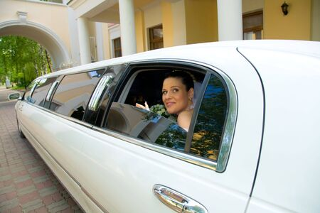 Photo of young happy woman looking out of white limousine window with arc on the background