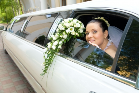Image of beautiful bride showing her rose bouquet out of wedding limousine and looking at camera photo