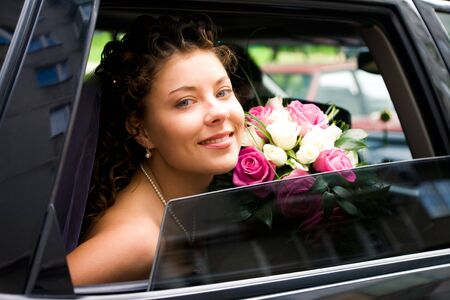 Photo of happy bride looking out of car window with bouquet in her hands photo