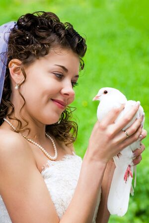 Photo of beautiful bride holding white dove in hands and looking at it with smile photo