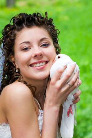 Portrait of happy bride holding white dove and cuddling it up to her cheek while looking at camera photo