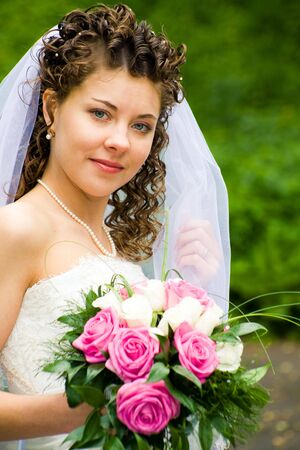 Portrait of beautiful bride with rose bouquet in hand looking at camera photo