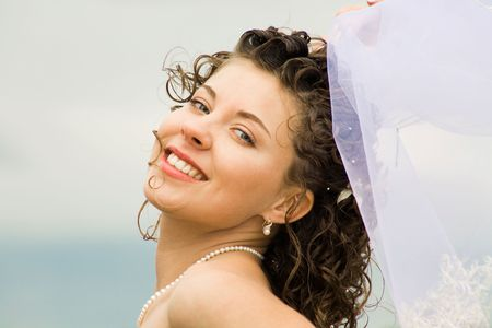 Image of happy young bride touching wedding veil and looking at camera  photo