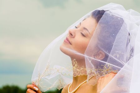 Photo of half-face of gorgeous happy bride isolated on a sky background   photo