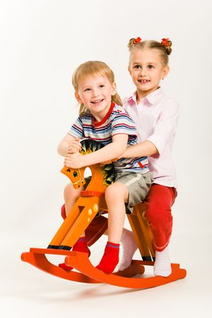 Photo of sister and brother sitting on the toy horse together Stock Photo - 3177793