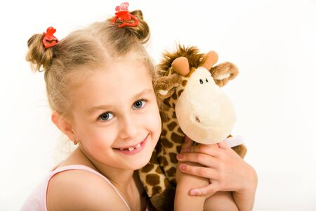 Portrait of beautiful young girl hugging toy giraffe photo