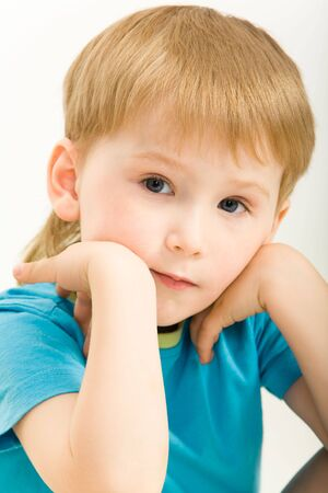 Portrait of pensive boy in blue t-shirt on a white background