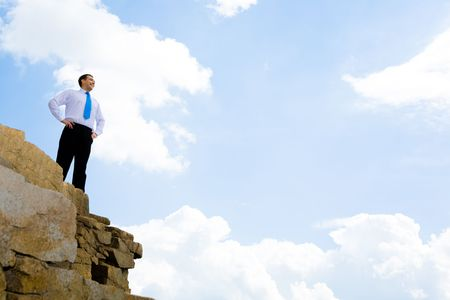 Photo of happy businessman standing on the cliff and looking into the distance on the background of bright sky photo