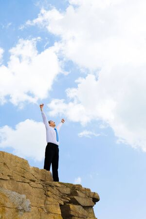 Photo of joyful businessman looking at bright sky with his arms raised expressing happiness and enjoyment photo