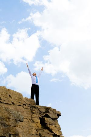 Image of cheerful businessman raising his arms upwards to the bright blue sky outdoors Stock Photo