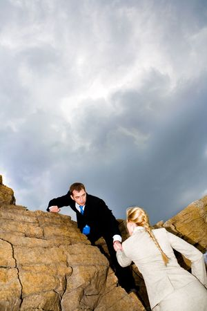 Photo of businessman in suit helping woman climb on the mount with storm-cloud above them Stock Photo