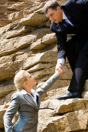 Image of businessman standing on the mount and holding blond woman by hand