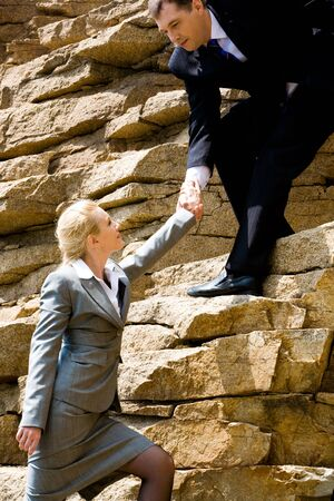 Image of helpful man holding businesswoman by hand while standing on the mountain photo