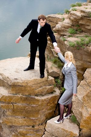 Conceptual image of business man helping to climb to mountain to his colleague photo