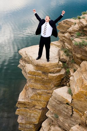 Portrait of happy businessman screaming and standing on the mountain  photo